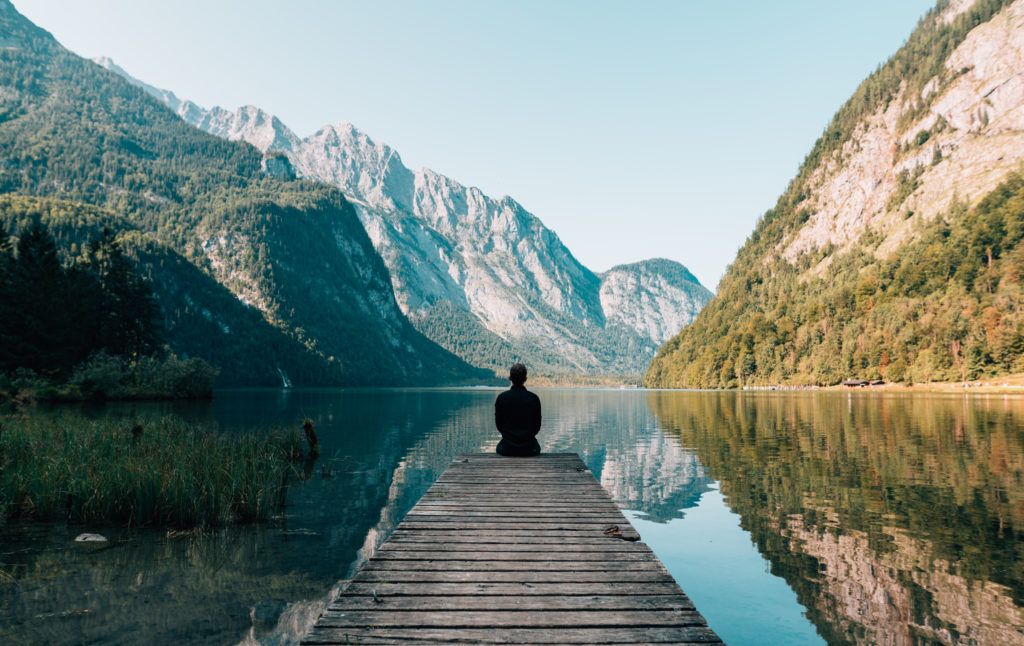 A person sits at the edge of a dock with their back turned to the viewer. The lake is surrounded by mountains.