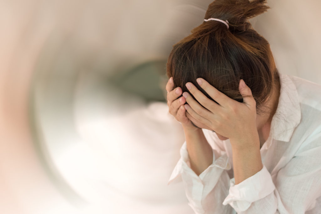 A picture of a woman with here head down and hands on her head, looking as if she is in distress.