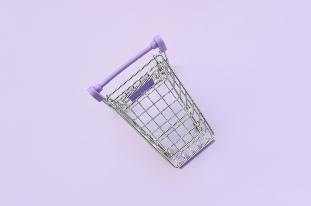 Small shopping cart lies on a violet background. Minimalism flat lay top view.