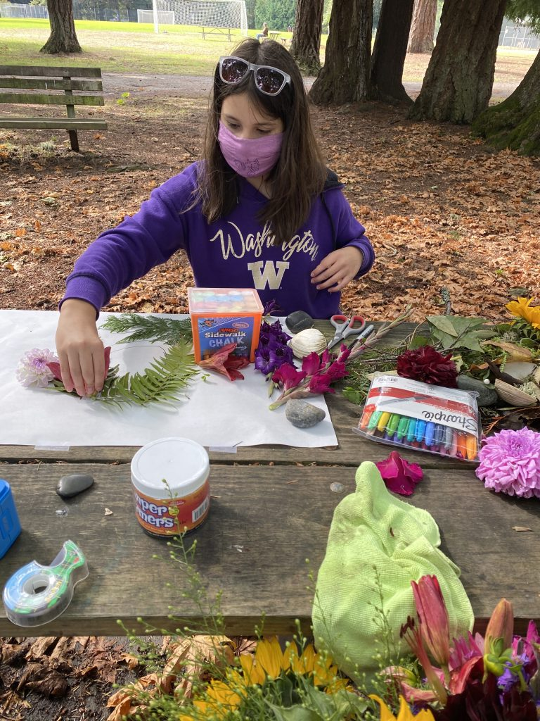 Picture of young girl with brown hair sitting at a picnic table using flowers and plants to create a self portrait